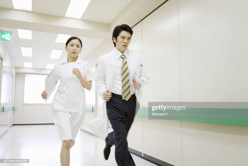 Doctor and nurse running in hospital corridor : Foto stock