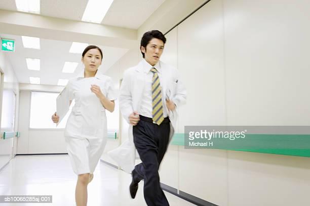 Doctor and nurse running in hospital corridor