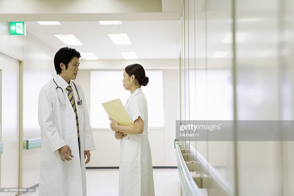 Doctor and nurse talking in hospital corridor : Foto stock
