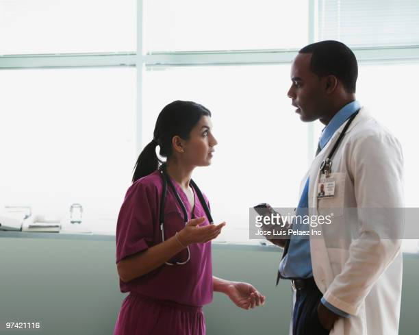 doctor and nurse talking in hospital hallway - american influenced stock photos and pictures