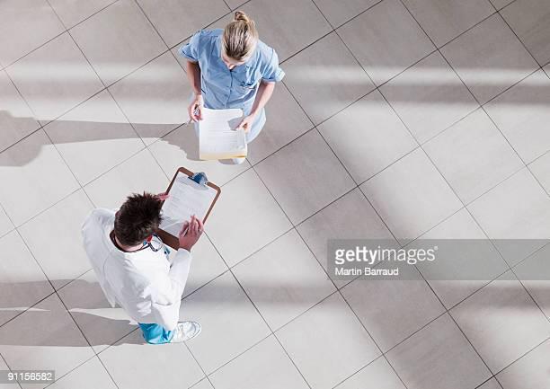 doctor and nurse talking in hospital lobby - vue en plongée verticale photos et images de collection