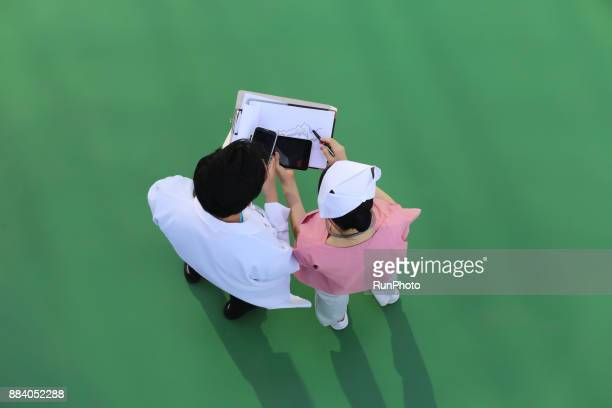 Doctor and nurse talking together with smartphone and digital tablet