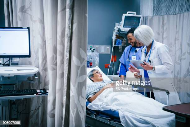 doctor and nurse talking with patient in hospital bed - emergency room stock pictures, royalty-free photos & images