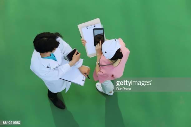 Doctor and nurse using digital tablet in meeting