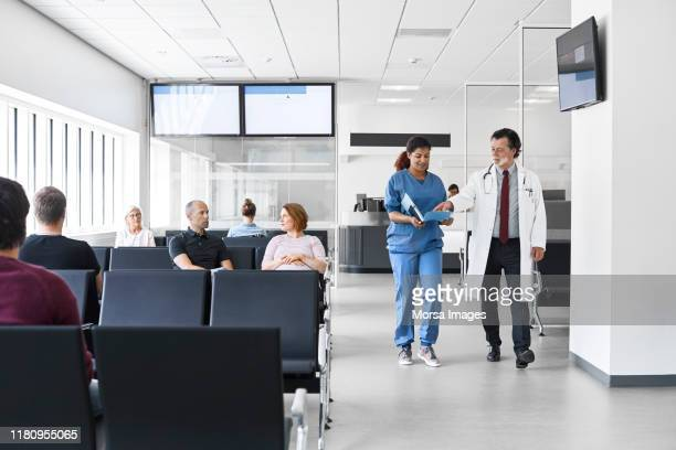 doctor and nurse walking by patients in lobby - outpatient care stock pictures, royalty-free photos & images