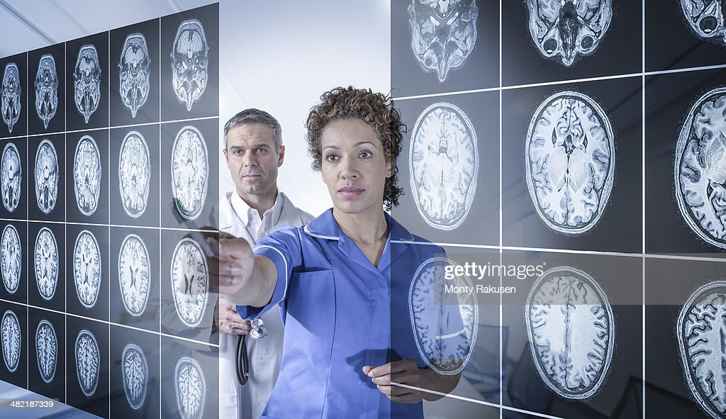 Doctor and nurse working with MRI brain scans seen through interactive display : Stock Photo