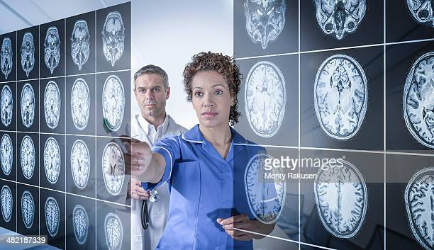 Doctor and nurse working with MRI brain scans seen through interactive display