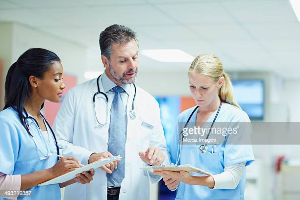 Doctor and nurses discussing over medical reports