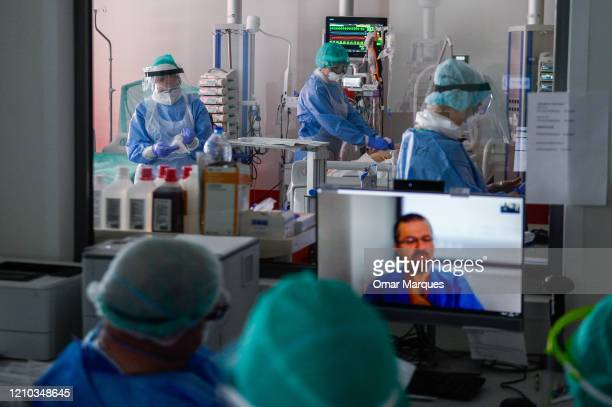 A doctor and nurses wear protective suits masks goggles and gloves as they take part in a video call inside the Intensive Care Unit for COVID19...