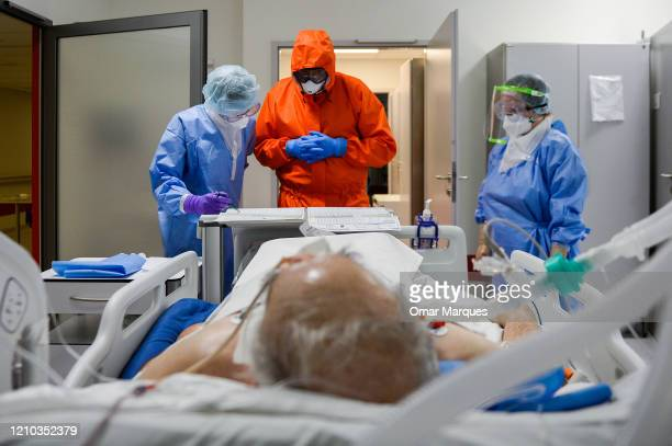 Doctor and nurses wear protective, suits, masks, goggles and gloves as they perform the morning medical checks inside the Intensive Care Unit for...