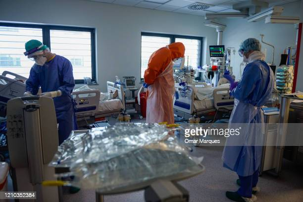 A doctor and nurses wear protective suits masks goggles and gloves as they perform the morning medical checks inside the Intensive Care Unit for...