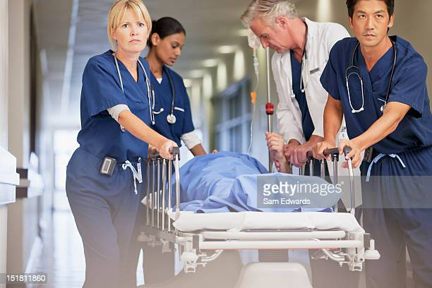 doctor and nurses wheeling patient in gurney down hospital corridor - urgency stock pictures, royalty-free photos & images