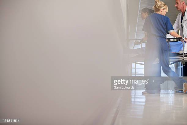 Doctor and nurses wheeling patient in hospital corridor