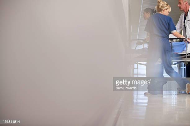 Doctor and nurses wheeling patient in hospital corridor