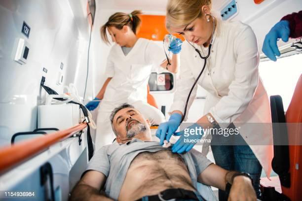 doutor e paramédicos que ajudam o homem maduro - vítima - fotografias e filmes do acervo