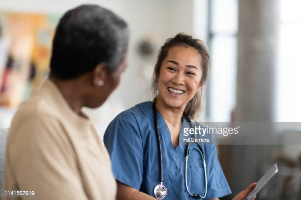doctor and patient having a conversation - visita imagens e fotografias de stock