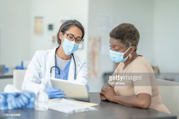 doctor and patient in medical exam - fatcamera stock pictures, royalty-free photos & images