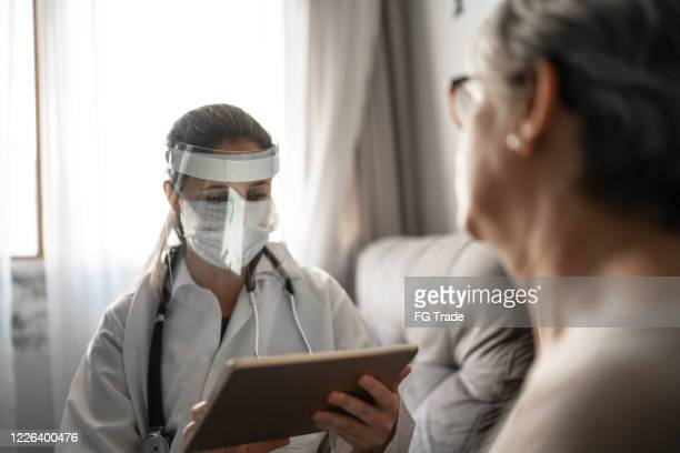 doctor and patient on medical consultation using digital tablet at patient's house - patient safety stock pictures, royalty-free photos & images