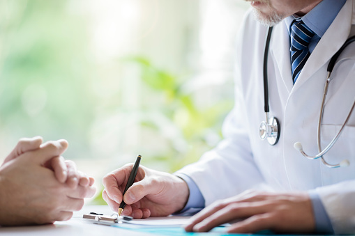 Doctor and patient taking notes in surgery 924365084