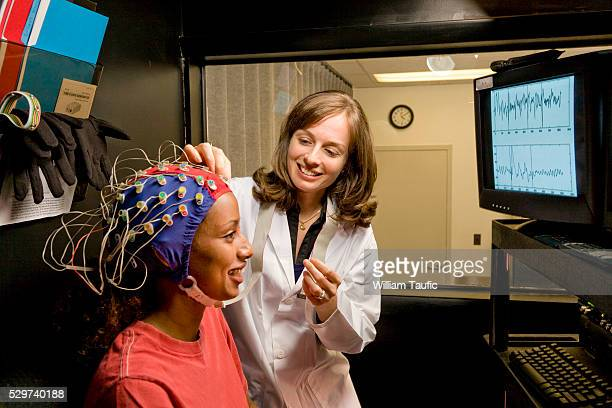 doctor and patient with electrodes on head - eeg stock pictures, royalty-free photos & images
