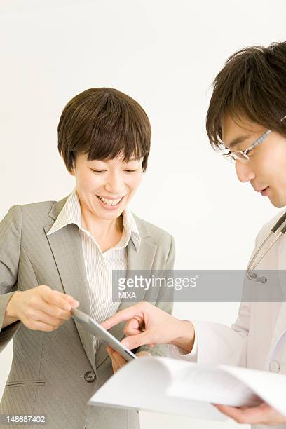 Doctor and pharmaceutical sales representative looking tablet computer