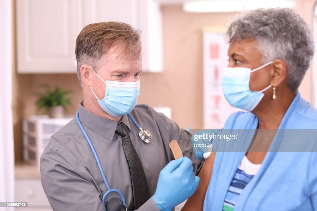 COVID-19: Doctor and senior adult, African descent patient, vaccine, masks. : Stock Photo