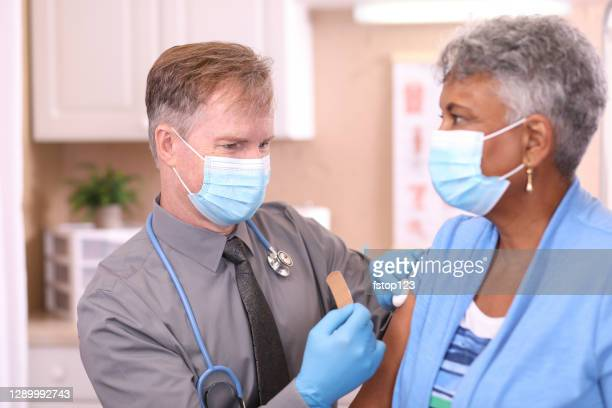 covid-19: doctor and senior adult, african descent patient, vaccine, masks. - covid 19 vaccine stock pictures, royalty-free photos & images