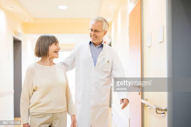 Arts en senior patiënt praten in de gang