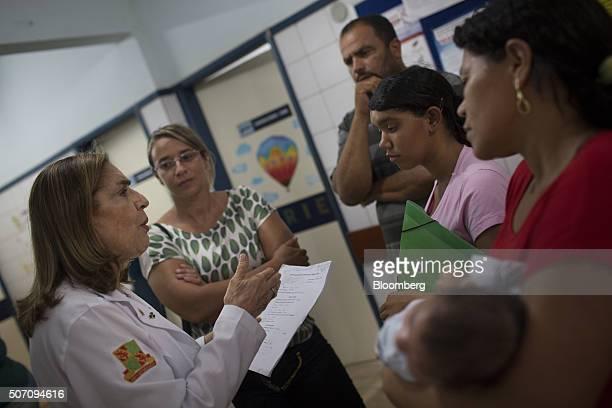 Doctor Angela Rocha left talks with the family of Julie Adriana center while onemonthold son Alexandro Julio is held by his grandmother right at the...
