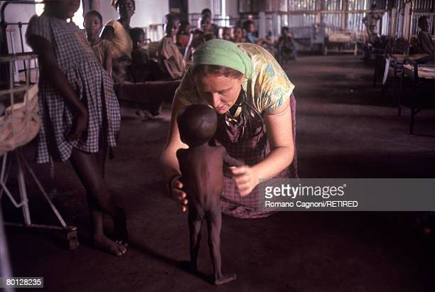 Doctor Ann Seymour helps an emaciated child barely able to stand on his legs to walk in Biafra a secessionist state in southern Nigeria circa 1970