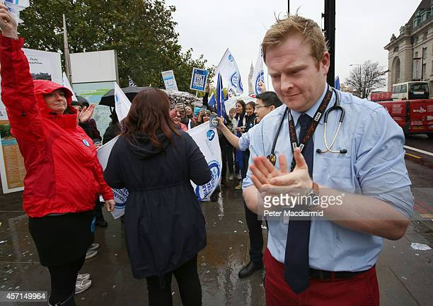 A doctor applauds National Health Service workers who are gathered outside St Thomas' Hospital on October 13 2014 in London England NHS workers are...