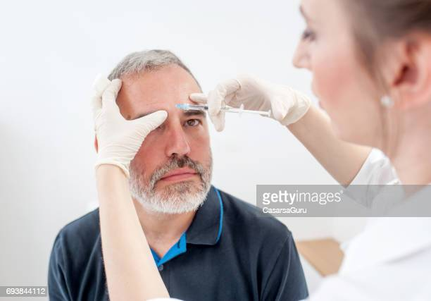 doctor applying botox therapy on patient face - botox stock pictures, royalty-free photos & images