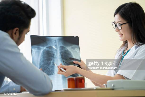 doctor asian women with patient looking at x-ray in office. - x ray image ストックフォトと画像