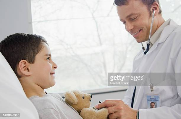 Doctor assisting boy (10-12) sitting in hospital bed with teddy bear