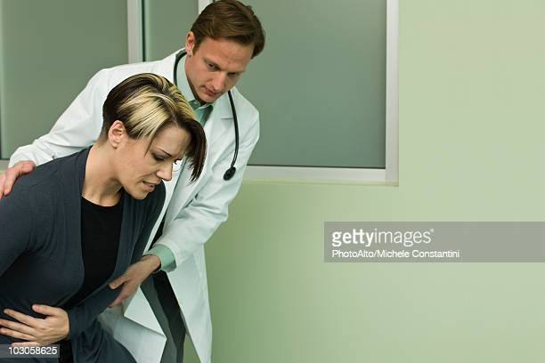 doctor assisting patient experiencing severe abdominal pain - appendicitis stock photos and pictures
