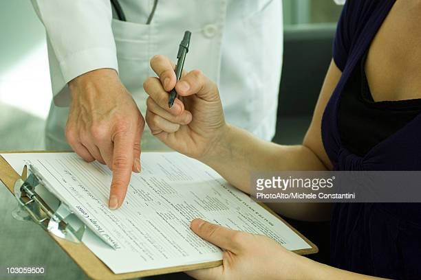 Doctor assisting patient with completing medical paperwork