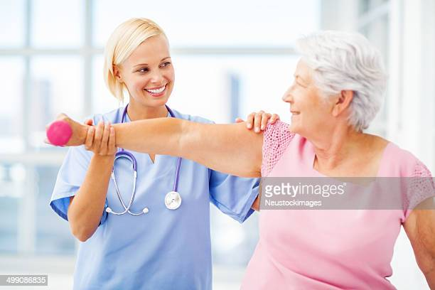 Doctor Assisting Senior Patient In Lifting Dumbbell