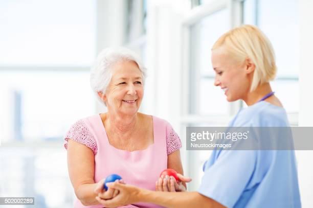 Arzt helfen Senior Patienten In Drücken Stress-Ball