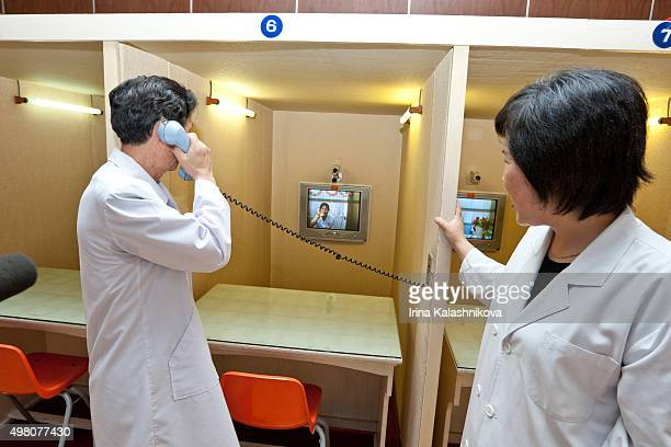 A doctor at Pyongyang Maternity Hospital talking over an internal phone with a patient As fathers are not allowed to meet directly with their wives...