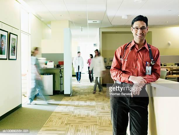 Doctor at reception desk smiling, portrait (blurred motion)