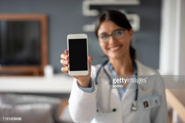 medico alla portata del cellulare - mostrare foto e immagini stock
