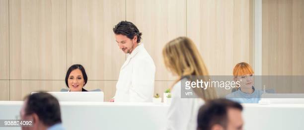 doctor at the reception desk - medical receptionist uniforms stock photos and pictures