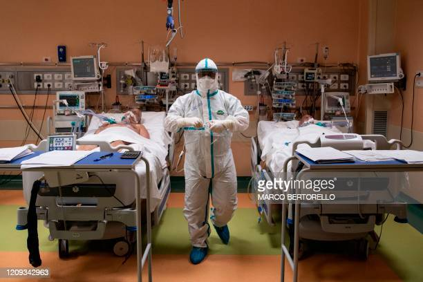 TOPSHOT A doctor attends to patients in intensive care in the COVID19 ward of the Maria Pia Hospital in Turin on April 7 2020 The Piedmont region...