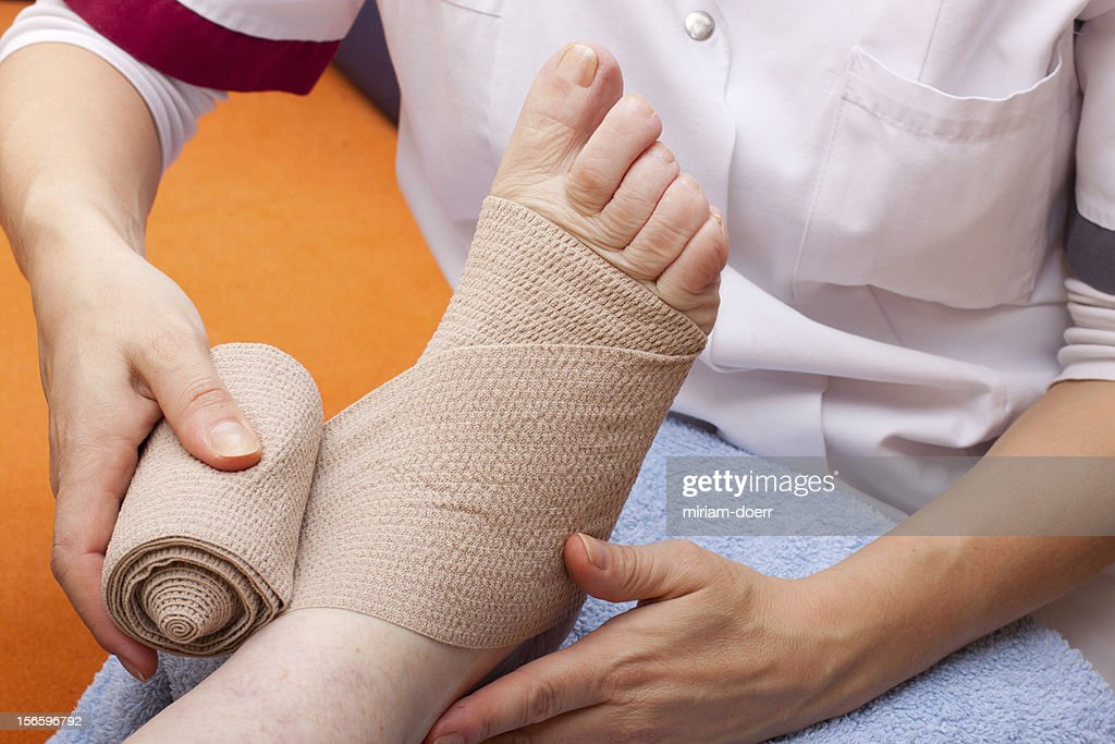 Doctor bandaged foot of a patient : Stock Photo