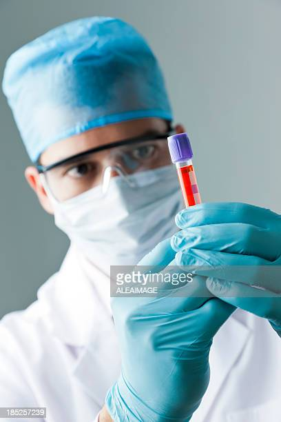 Doctor, Bioanalyst or Scientist, looking at a test tube