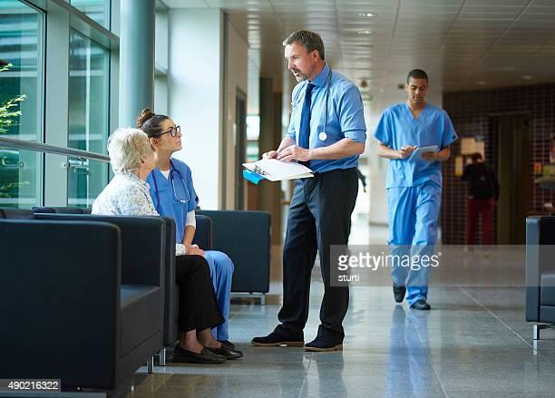 Arzt unterhalten zu einem Patienten im Krankenhaus-Korridor.