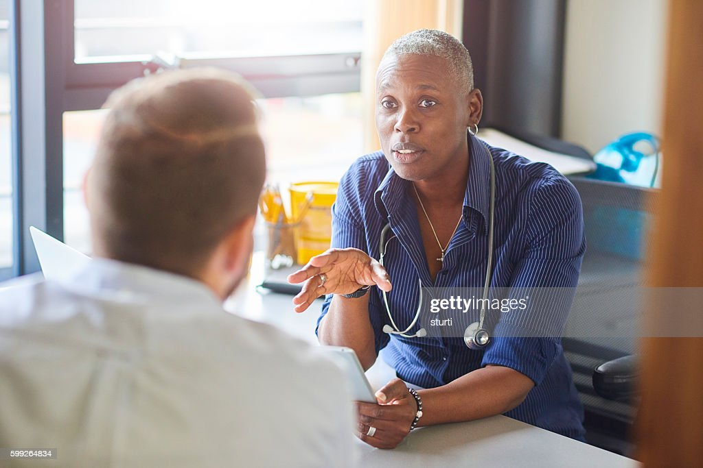 Doctor chatting to male patient : Stock Photo