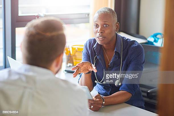 doctor chatting to male patient - female doctor stock photos and pictures