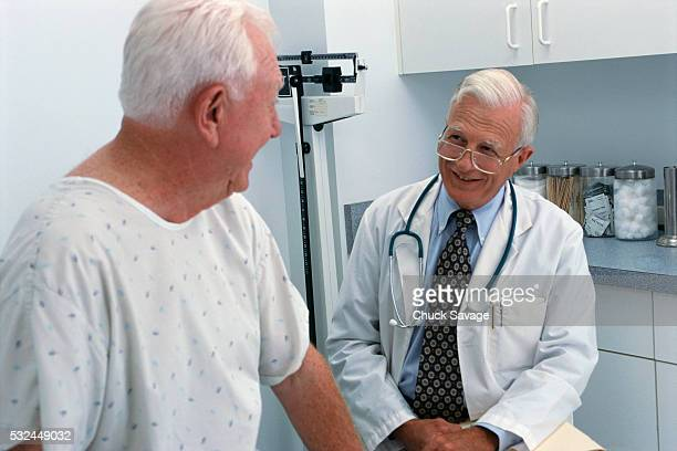 doctor chatting with patient in exam room - gerontology stock pictures, royalty-free photos & images