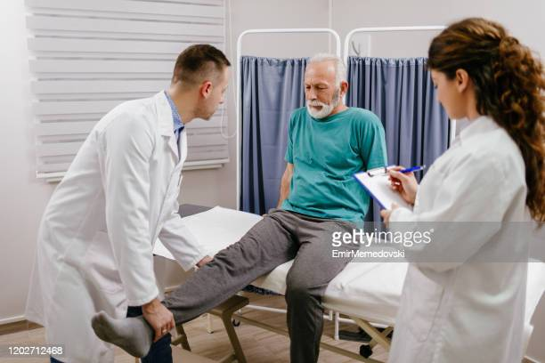 doctor checking a leg injury on a senior male patient - rheumatism stock pictures, royalty-free photos & images